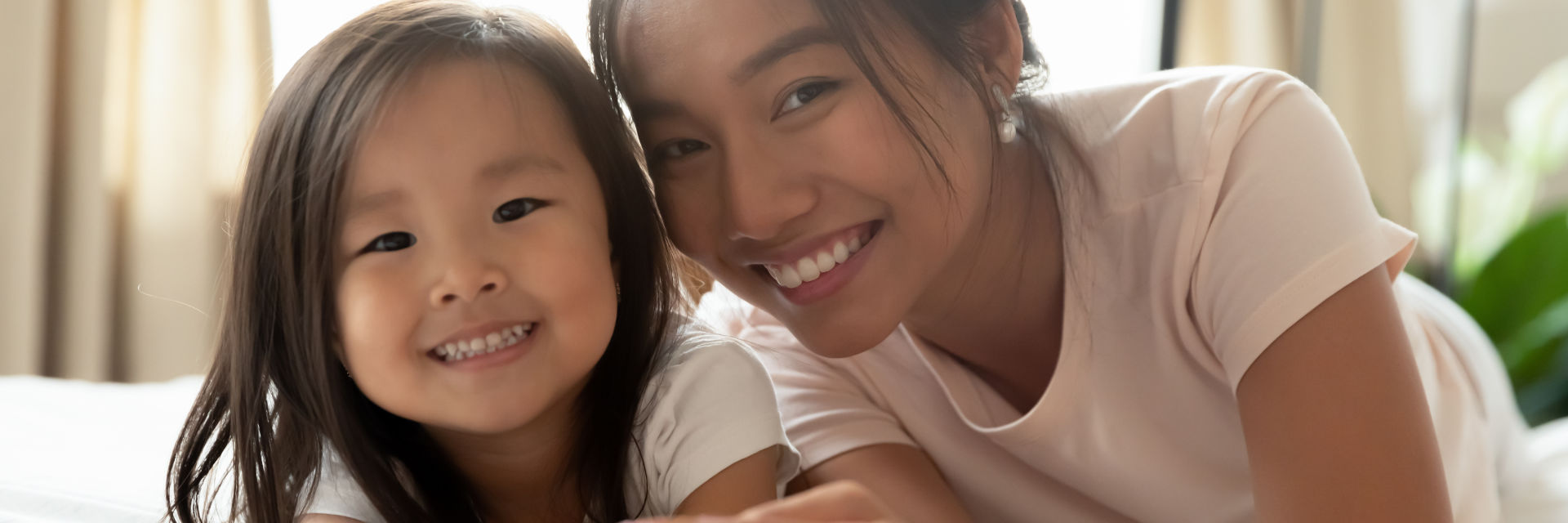 A happy Asian woman and her little daughter showing nice teeth in their smiles.
