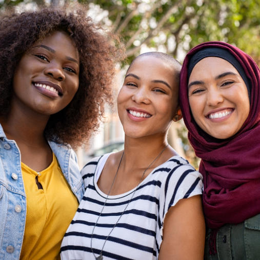 A group of three multi-cultural women with perfect smiles.