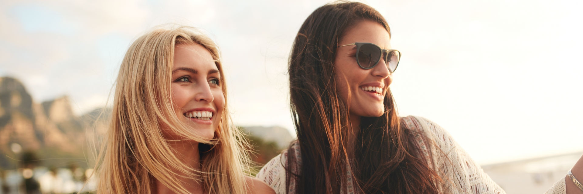 Two happy women with perfect smiles spending their time outdoors.