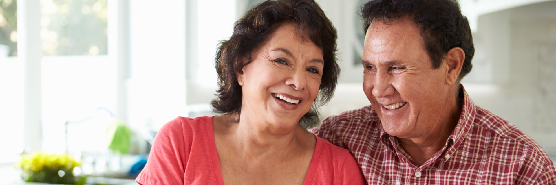 A broadly smiling senior couple showing their teeth after dental restoration procedures.