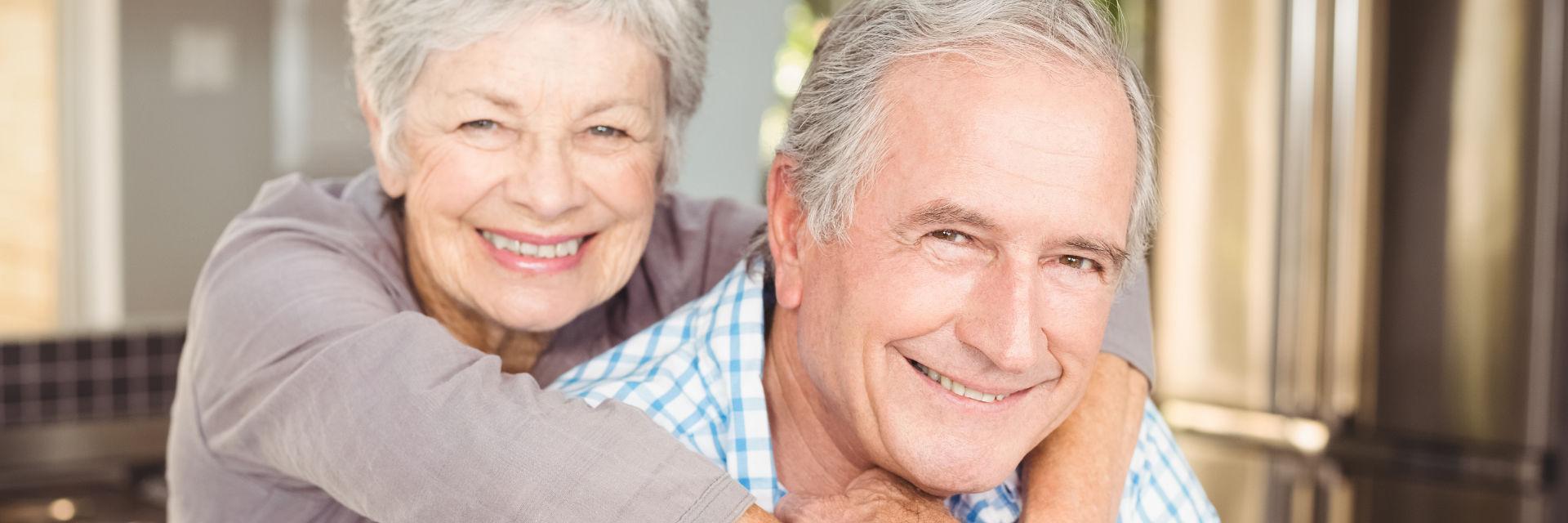 A broadly smiling senior couple.