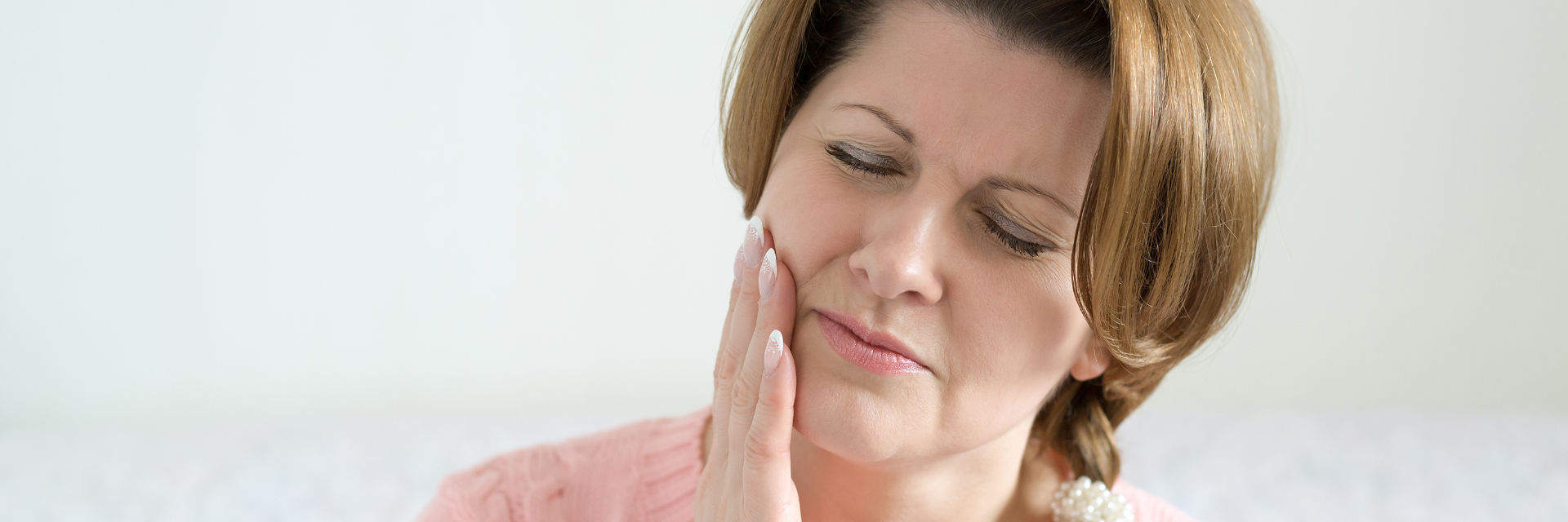 A woman with dental pain in need of emergency dental appointment.