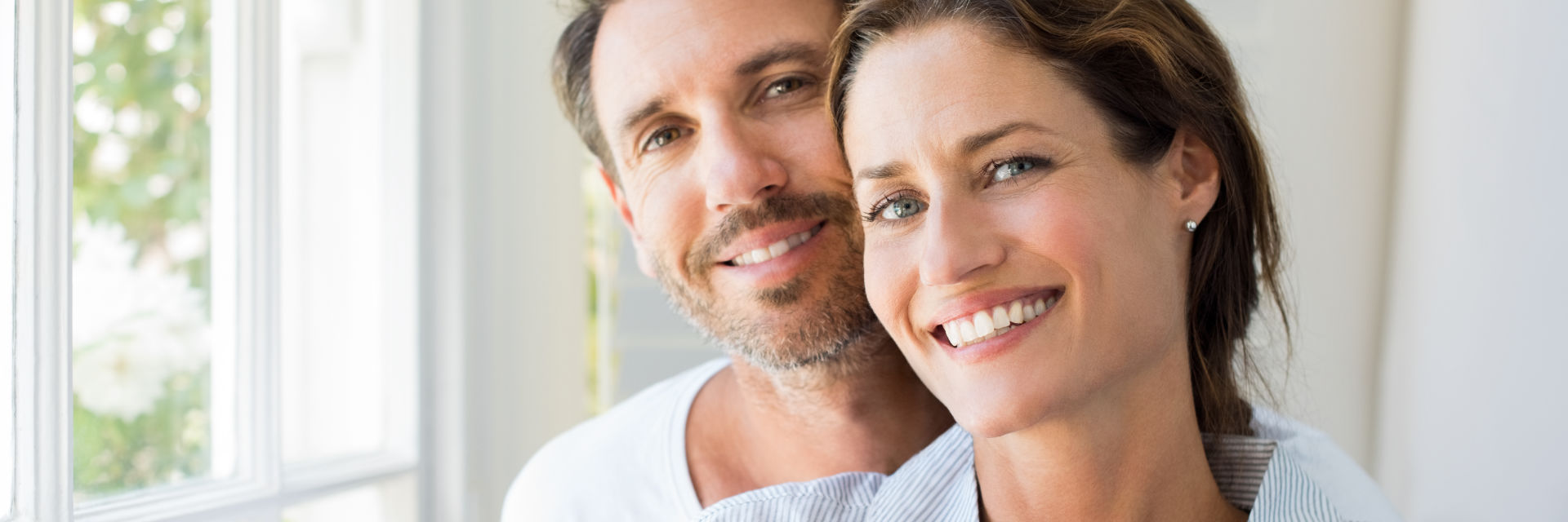 Happy middle-aged couple showing their nice healthy teeth in their smiles.