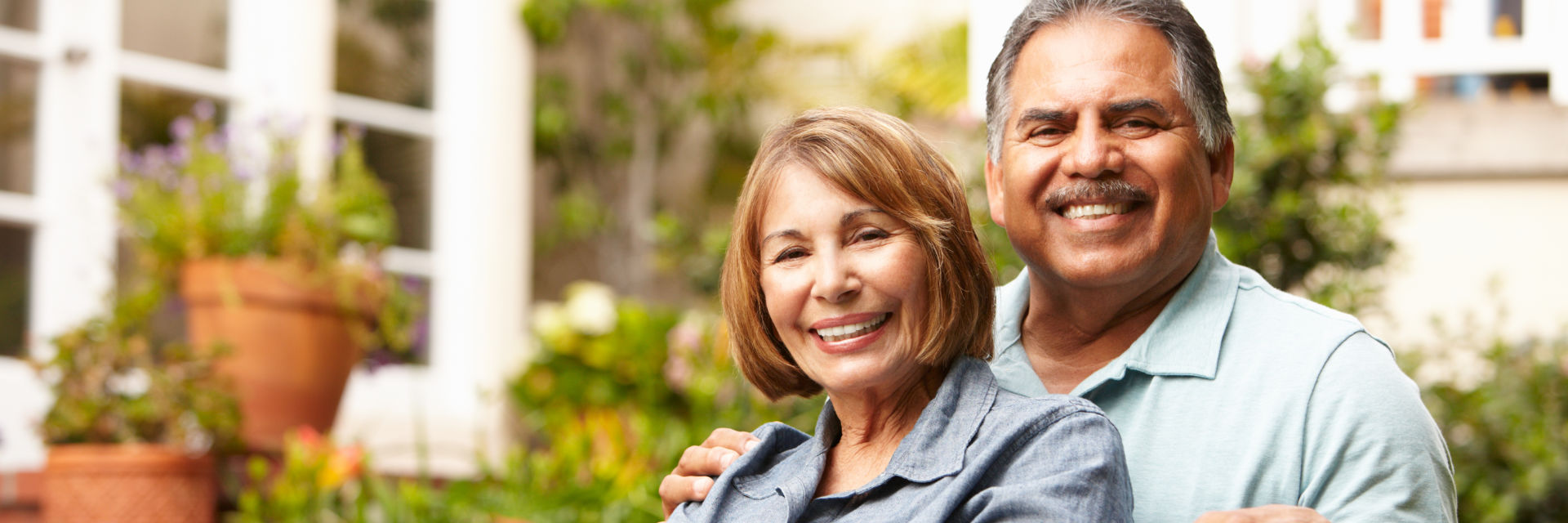 A happy senior Hispanic couple with perfect smiles in front of their house.
