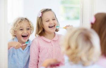 Two happy little children in pajamas having fun brushing their teeth